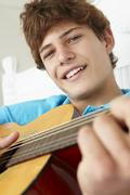Teenage boy playing acoustic guitar Stock Photos