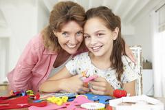 Young girl doing handicrafts with grandmother Stock Photos