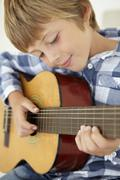 Young boy playing acoustic guitar Stock Photos