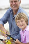 Young boy fishing with grandfather Stock Photos