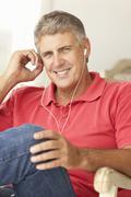 Mid age man wearing earphones - stock photo
