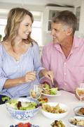Mid age couple enjoying meal at home Stock Photos
