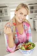 Teenage girl eating salad - stock photo