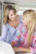 Mother and teenage daughter using laptop Stock Photos