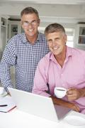 Mid age men working on laptop at home - stock photo