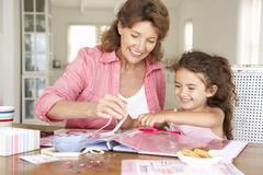 Senior woman scrapbooking with granddaughter - stock photo