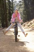 Woman freewheeling down country lane Stock Photos