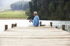 Senior man fishing on jetty Stock Photos