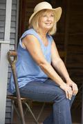Senior woman sitting on veranda Stock Photos
