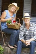 Senior couple sitting on veranda with flowers Stock Photos