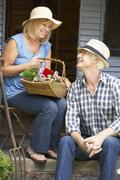 Senior couple sitting on veranda with flowers Stock Photos