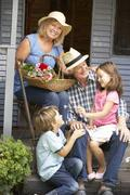 Senior couple on veranda with grandchildren Stock Photos