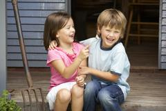 Young brother and sister sitting on veranda Stock Photos