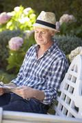 Mid age man reading newspaper in garden - stock photo