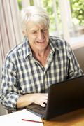 Mid age man working in home office - stock photo