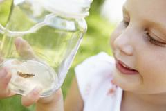 Little girl with cricket in a jar - stock photo