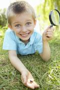 Young boy with beetle and magnifying glass - stock photo