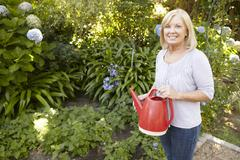 Senior woman watering garden Stock Photos