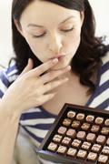 Woman eating chocolates Stock Photos