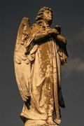 A statue of a male angel holding a cross, gazing up. - stock photo