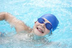 Boy swimming in outdoor pool - stock photo
