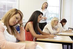 Students and tutor in exam Stock Photos