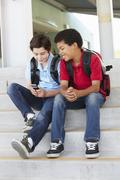 Pre teen boys with phone at school - stock photo