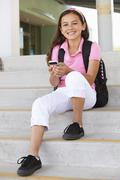 Pre teen girl with phone at school Stock Photos