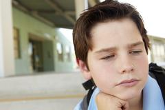 Unhappy Pre teen boy at school Stock Photos