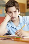 Unhappy boy in art class - stock photo