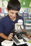 Boy in science class with microscope - stock photo