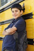 Pre teen boy with school bus - stock photo