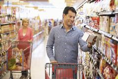 People shopping in supermarket - stock photo