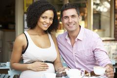 Expectant couple sitting outside café Stock Photos