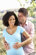 Expectant couple outdoors in countryside Stock Photos