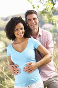 Expectant couple outdoors in countryside - stock photo