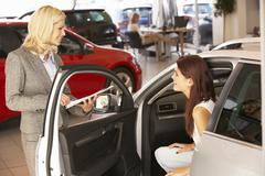 Young woman buying new car - stock photo