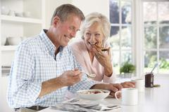 Retired couple eating breakfast - stock photo