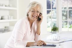 Retired woman with household bills - stock photo