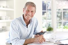 Retired man with household bills - stock photo