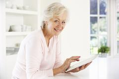 Senior woman using tablet at home Stock Photos