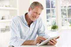 Senior man using tablet at home Stock Photos
