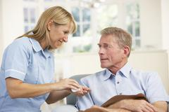 Senior man visited at home by nurse - stock photo