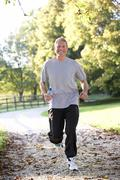 Senior man running in park Stock Photos