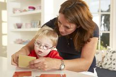 Downs Syndrome boyhaving speech therapy - stock photo