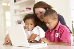 Mother and Downs Syndrome son with laptop - stock photo