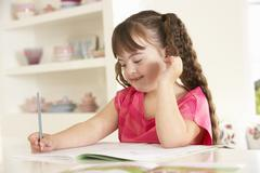 Girl with Downs Syndrome drawing - stock photo