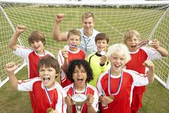 Winning junior football team portrait with coach - stock photo