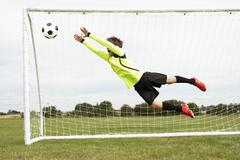 Boy goalkeeper jumping to save goal Stock Photos