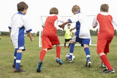 Junior 5 a side teams playing football - stock photo